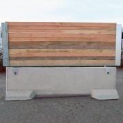 Clôture chantier avec habillage bois horizontal - Socle stabilisateur béton avec le cadre métallique et un habillage bois horizontal